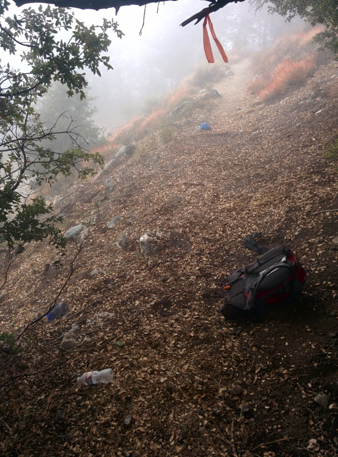 A backpack and hiking gear abandoned in the middle of the trail.
