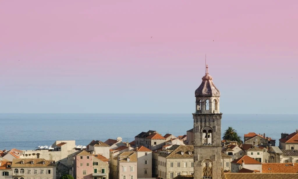 The Dubrovnik skyline with one church tower sticking up. The sky is pink at the top and blue at the bottom.