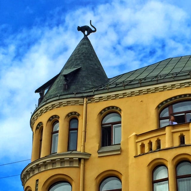 A yellow crenellated building in Riga. Its turret is topped with a black metal cat.