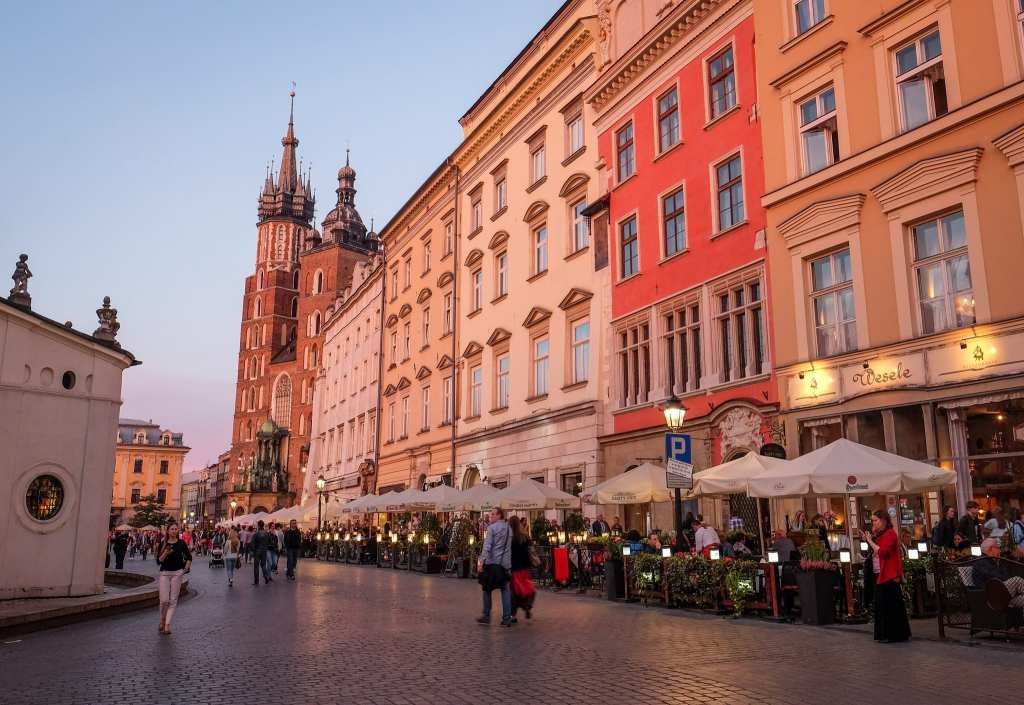 A row of buildings in Krakow, Poland, lit up with a pink tinge at sunset, ending with a church tower.