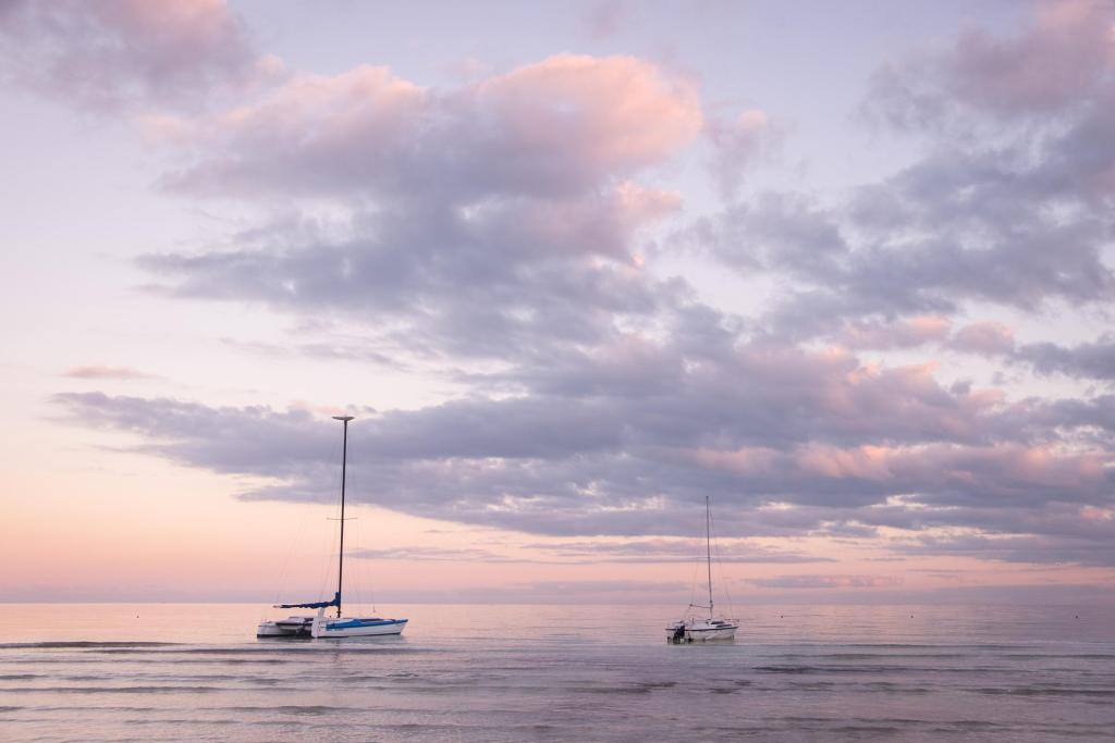 Purple and pink sunrise with two sailboats on the water at Holbox