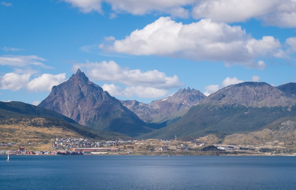 A view of triangular-shaped mountains in front of the still Beagle Channel in Ushuaia.