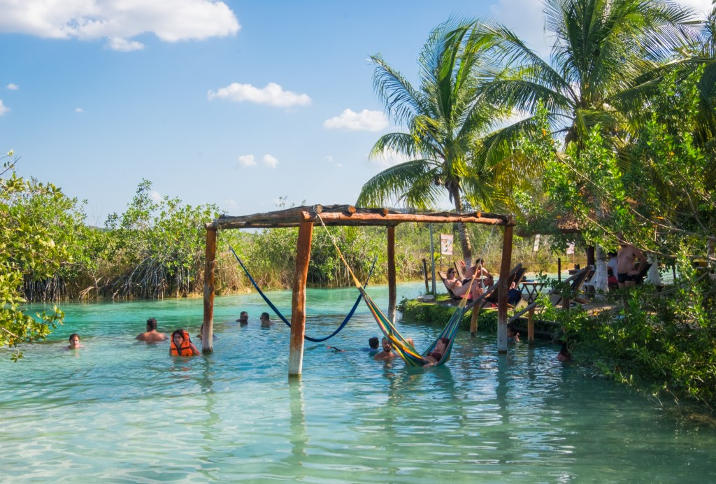 Hammocks in the bright blue water at Los Rapidos, Bacalar