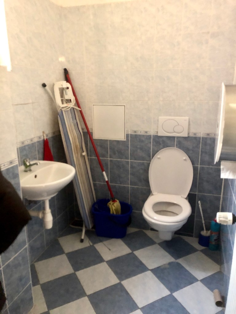 A tiny bathroom with toilet, sink, and an ironing board and mop leaning against the wall.