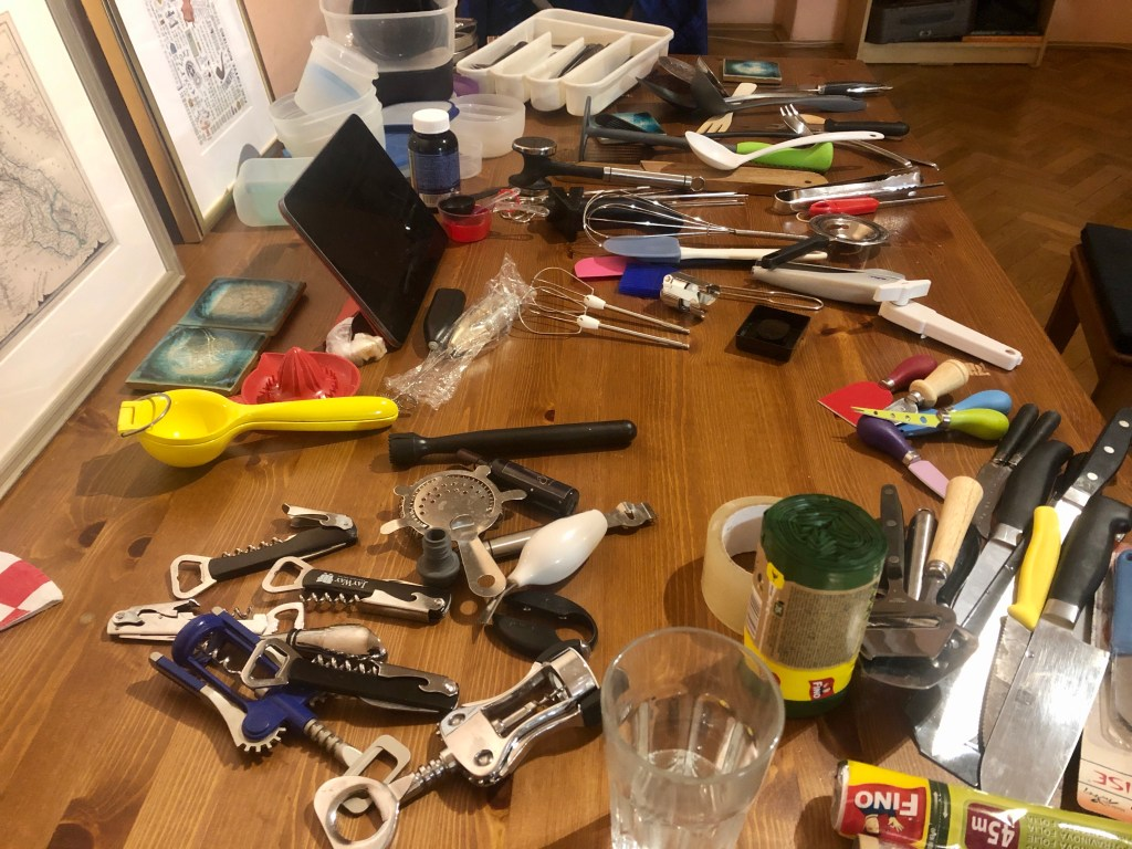 A table filled with miscellaneous kitchen tools: corkscrews, beaters, knives, all grouped by category.
