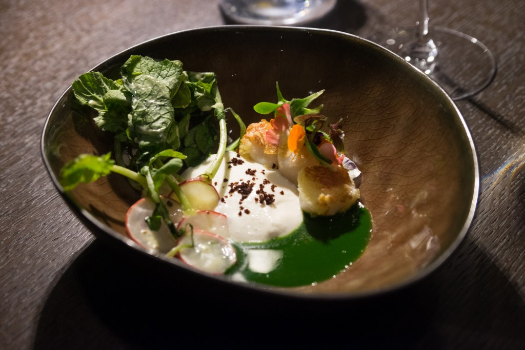 A brown ceramic bowl filled with three fried scallops and some greens, horseradish sauce, radishes, and green sauce.