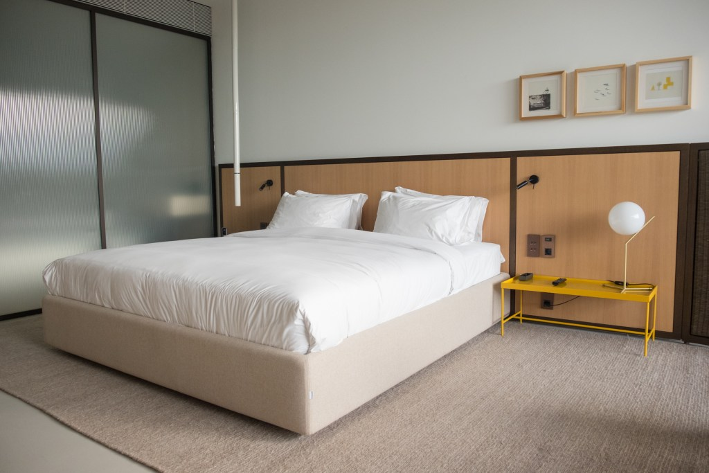 A simple room with a big white bed, yellow metal side table, and three natural wood framed prints on the wall.