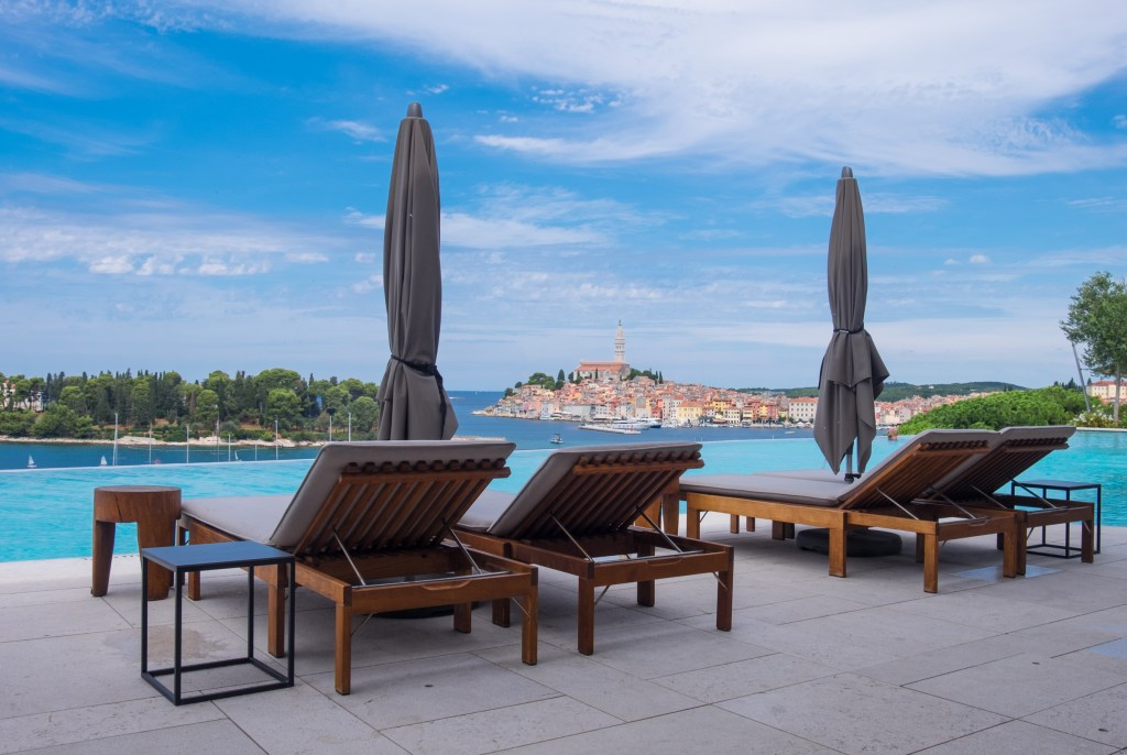 Four lounge chairs in front of the infinity pool with the city in the distance.