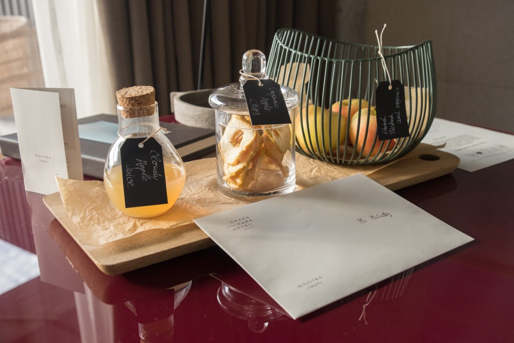 """Gifts at the hotel: an envelope reading """"Ms. McCulley"""" plus a container of cloudy apple juice, a clear jar filled with apple rings, and a wire fruit basket filled with apples."""