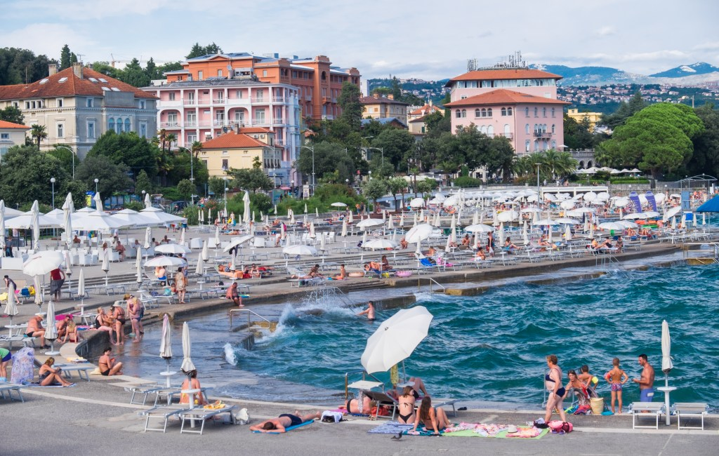 Beachgoers sitting on a concrete slab on the edge of a bright blue ocean in Opatija, Croatia, with Hapsburg-style ornate pink and orange buildings in the background.