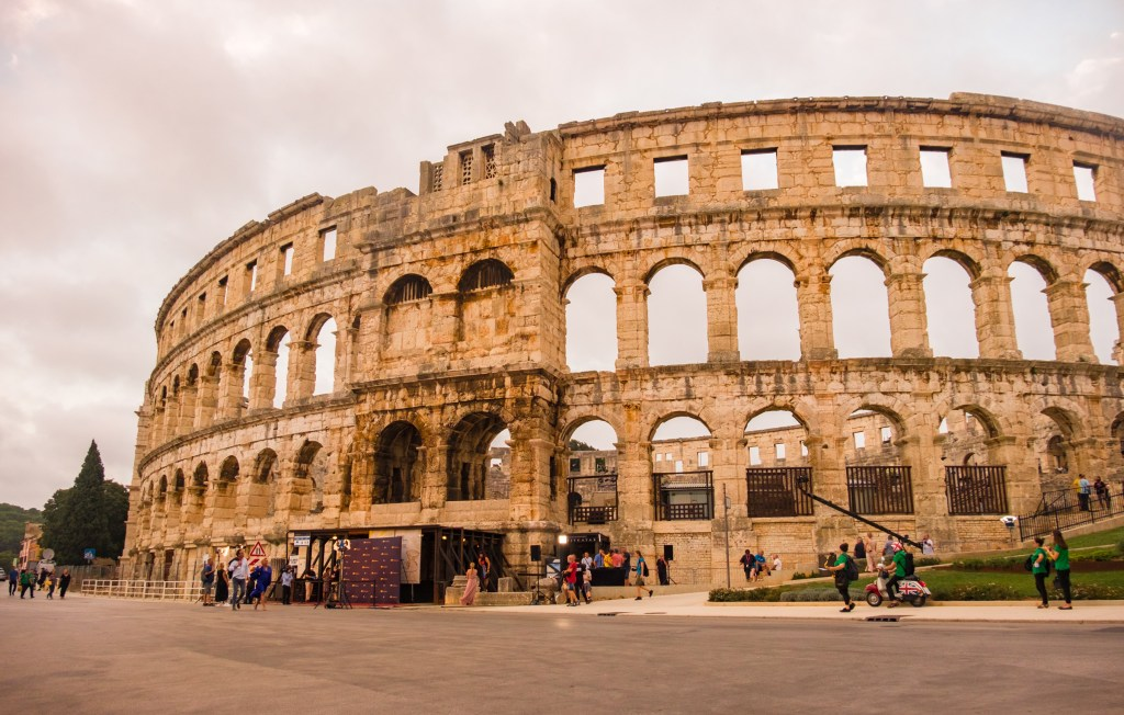 Pula's enormous Roman amphitheater, looking almost the same as in roman times, some people around the edge (including one guy inexplicably on a moped with a Union Jack flag).