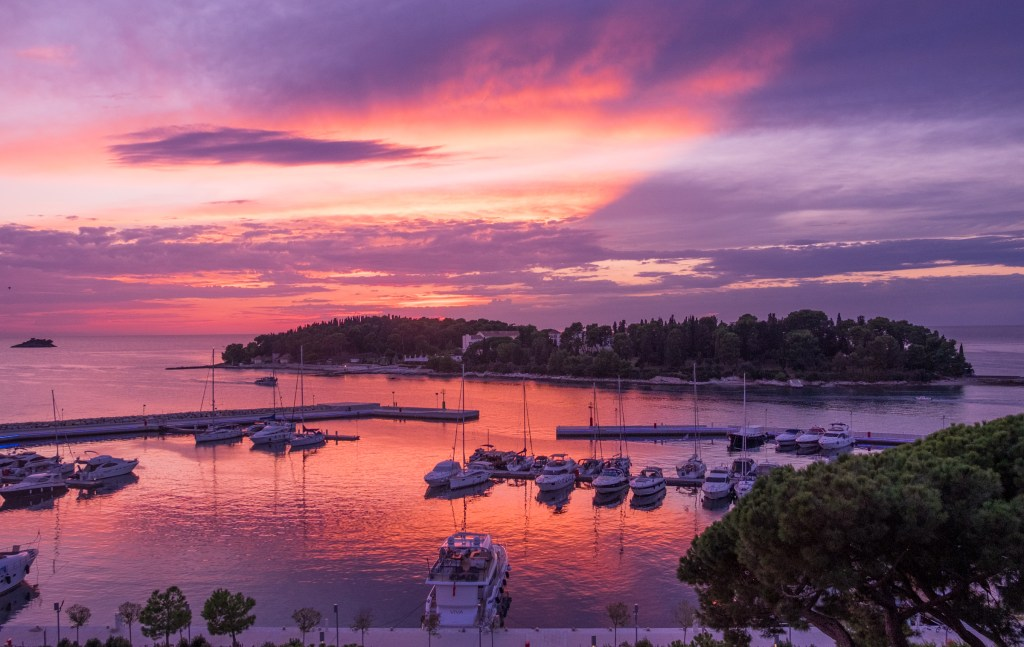 A purple and pink sunset behind a small green island; in the foreground, boats docked at piers.