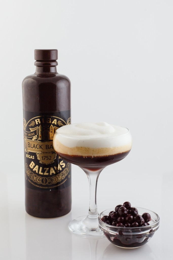 A dark brown bottle of Black Balsam liqueur with a black and gold label, a cocktail with a frothy white top, and a small bowl of dark brown berries.