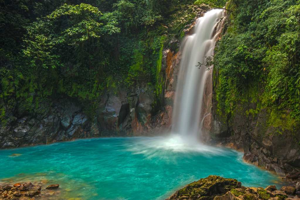 A waterfall in the middle of a jungle, flowing into a bright turquoise pool.