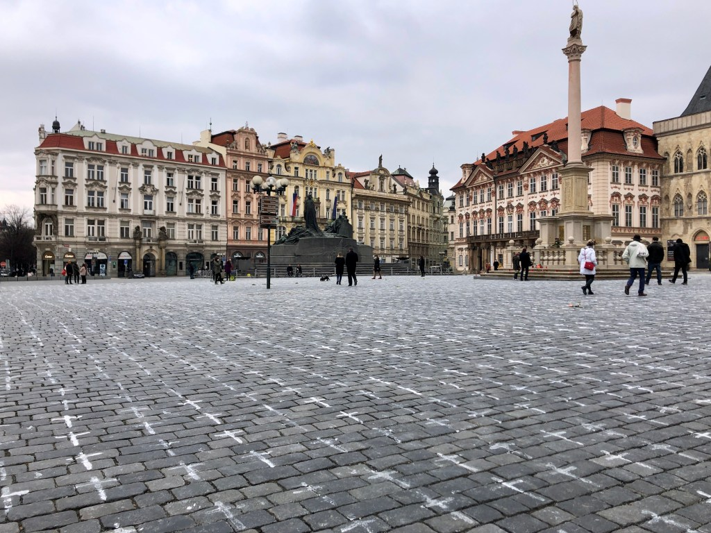 Old Town Square in Prague, edged with cream, pink and yellow crenellated buildings. In the foreground, you see the gray brick ground is covered with hundreds of white crosses, one for each Czech COVID victim.