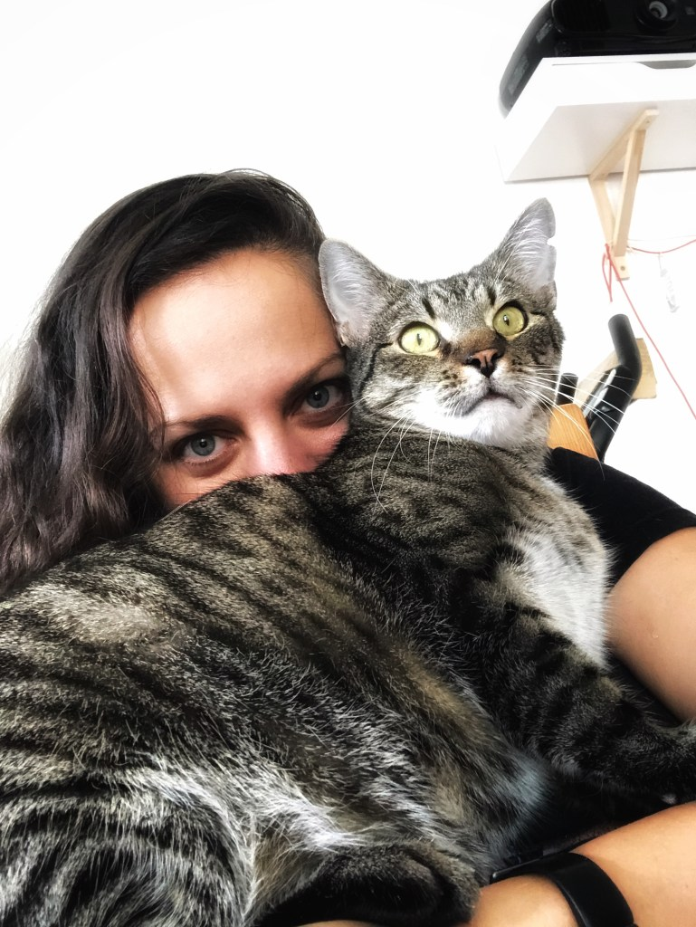 Kate holds Baliček the gray tabby cat in front of her face; you can only see her eyes peeking out from above his fur. Baliček stares straight ahead.