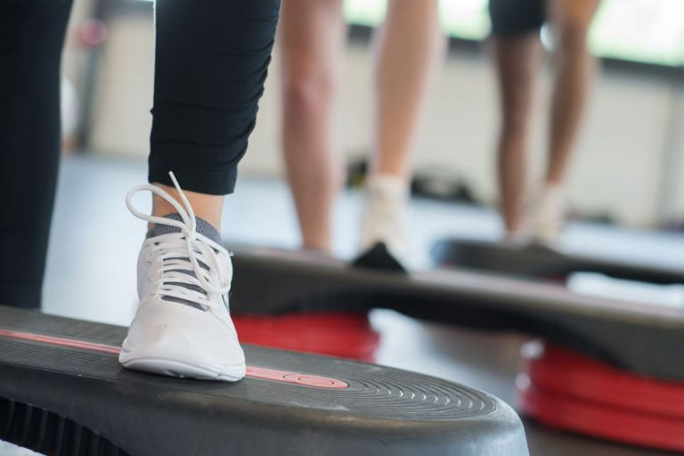 close up of women legs exercising with steppers in gym