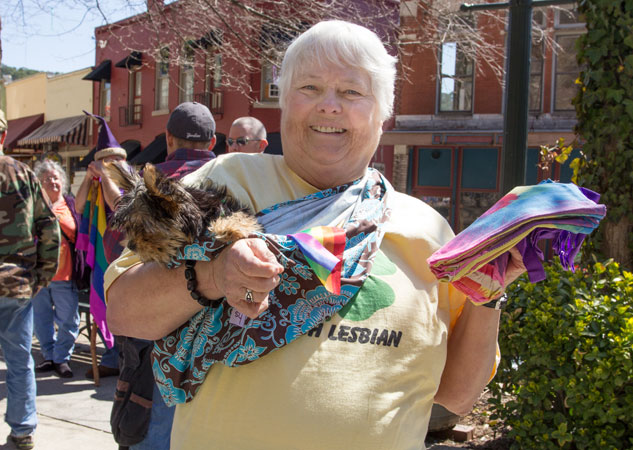 Woman holding a dog and rainbow hanky