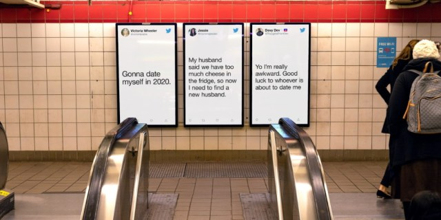 An escalator in front of a screen with tweets displayed on them