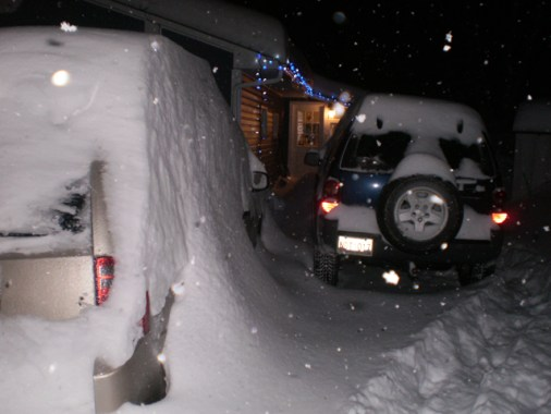 Cars under snow wiff house in bkg.