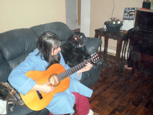 Cathi, guitar and Dog on the couch.