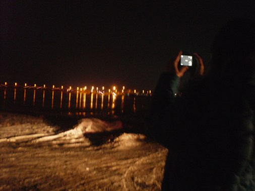 City lights, reflections, dimly lit snow, shadow of a person taking a photo on the right.