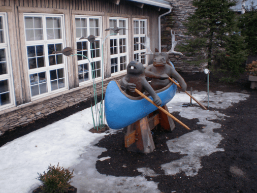 Beaver and moose Sculpture, paddling a blue canoe.