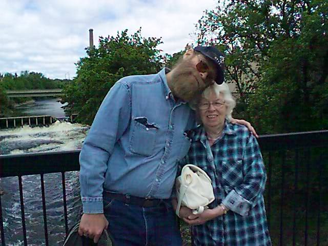 tall guy with his arm around his mother's shoulders on a bridge with a river with waterfalls as backdrop.