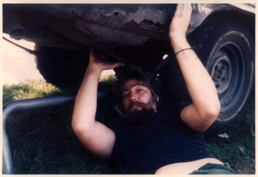 large strong looking guy on his back working on the underside of a car.