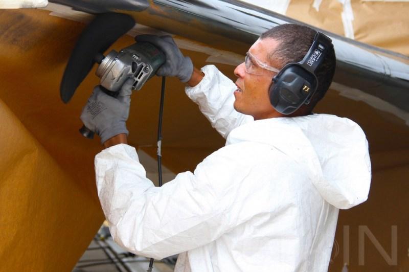 Profissional trabalha na asa de um Embraer 145.