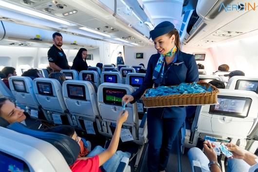 A comissária Ana distribui fones de ouvidos aos passageiros antes do voo