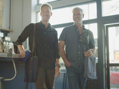 Aerrem co-founders, Steve Bauerfeind & Paul Kradin in a coffee shop with their Aerrem bags