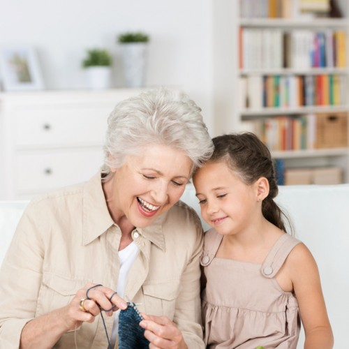 Senior lady teaching her granddaughter to knit as they relax together on the the sofa laughing together with enjoyment