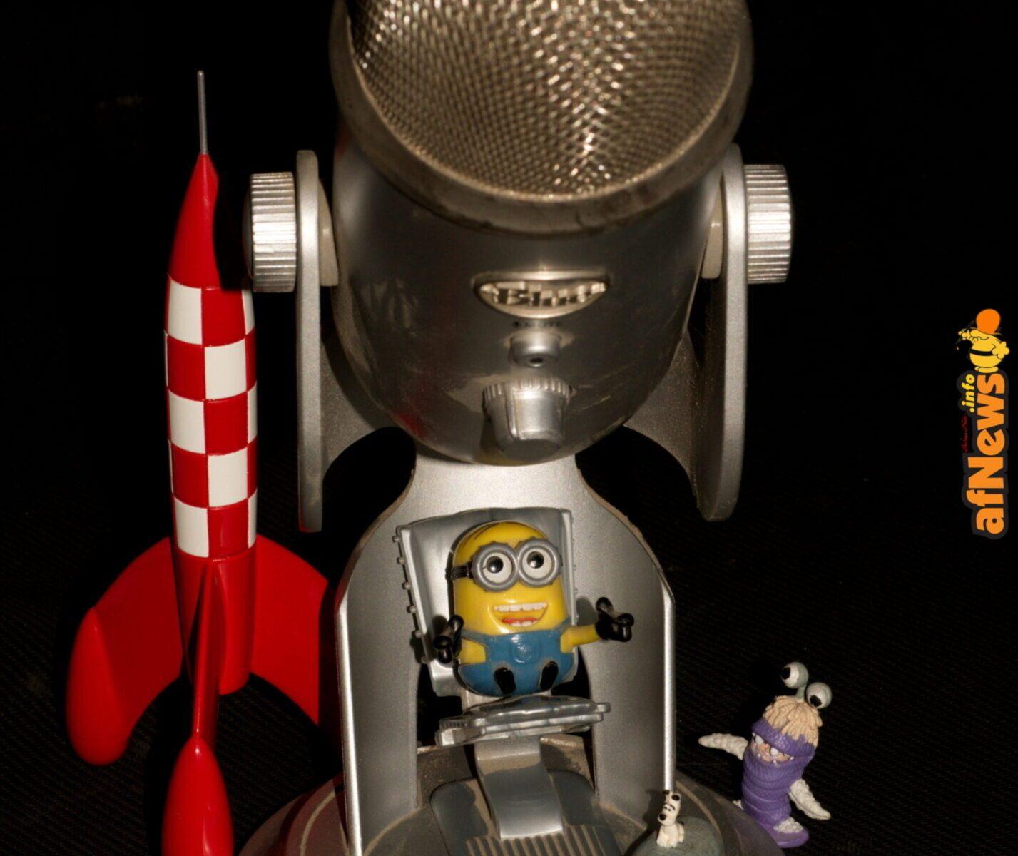 Fumetto su Fumetto, serie fotografica di Gianfranco Goria. Minion sotto microfono Blue con Razzo Tintin, Idefix su menhir e Boo travestita da mostro.