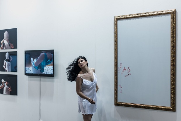 German performance artist of Turkish origin, Nezaket Ekici creates an artwork during the opening of the Art Basel art fair for a VIP preview in Hong Kong on March 13, 2015. Hong Kong's biggest art fair, Art Basel, opened its doors to an expected  thousands of visitors over five days.