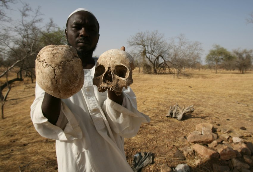 ** FILE ** In this Monday, April 23, 2007 file photo, Sudanese Darfur survivor Ibrahim holds human skulls at the site of a mass grave where he says the remains of 25 of his friends and fellow villagers lie, on the outskirts of the West Darfur town of Mukjar, Sudan. The International Criminal Court issued an arrest warrant Wednesday, March 4, 2009 for Sudanese President Omar al-Bashir on charges of war crimes and crimes against humanity in Darfur. (AP Photo/Nasser Nasser, File)