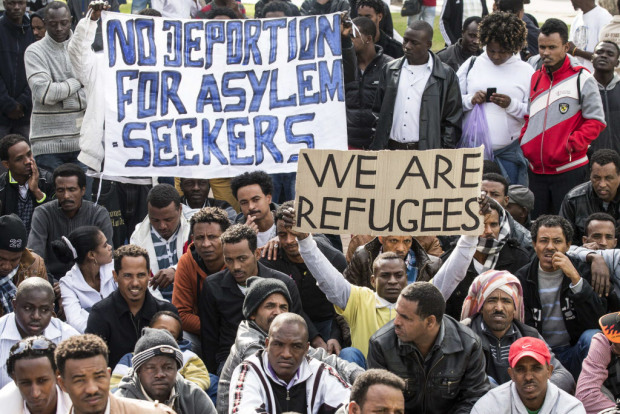 Protestors hold up signs in English as thousands of African asylum seekers who entered Israel illegally via Egypt staged a protest in Tel Aviv on January 7, 2014, slamming the Jewish state's long-term detention of illegal immigrants. The migrants, primarily from Eritrea and Sudan, are protesting for the third day in a row to call for help in the face of Israel's refusal to grant them refugee status and its detention without trial of hundreds of asylum seekers. AFP PHOTO / JACK GUEZJACK GUEZ/AFP/Getty Images