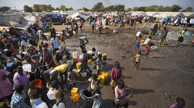 FILE - In this Sunday, Dec. 29 2013 file photo, displaced people gather around a water truck to fill containers, at a United Nations compound which has become home to thousands of people displaced by the recent fighting, in the capital Juba, South Suda. Sudan's political limbo continued Friday, Aug. 19, 2016 after rebel leader Riek Machar fled the country earlier in the week. Last month government and rebel forces clashed in the capital, killing hundreds of civilians and Machar was controversially removed as First Vice President. Machar's departure puts South Sudan's peace deal into disarray at the same time the country is suffering from a humanitarian crisis. (AP Photo/Ben Curtis,file)