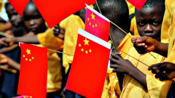 Bimbi tanzaniani sventolano bandierine cinesi di benvenuto al loro partner orientale