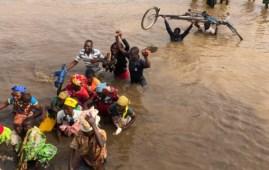 Chimoio, Mozambico. Persone si affrettano ad attraversare un fiume per andare alla prima distribuzione di cibo più di due mesi dopo il ciclone. (Foto © courtesy Devon Cone, Refugees International)