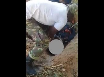 Uomo con uniforme militare sta decapitando un cadavere in una fossa comune a Cabo Delgado