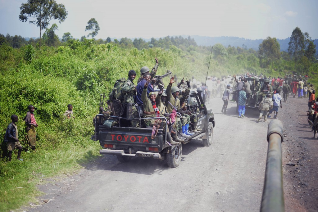 FARDC Colonel Mamadou's vehicle arriving and heading to the front of the procession in Rugare about 5 or 10 km from Rumangabo. The colonel got out just in front and marched / ran along with the population for a couple of kilometres. On arrival at the turn off to Rumangabo, the colonel got out of the car again and advanced the 5 or so km up the hill through the town to Rumangabo military camp followed by a tank and surrounded by six of his close soldiers. [JOSEPH KAY]