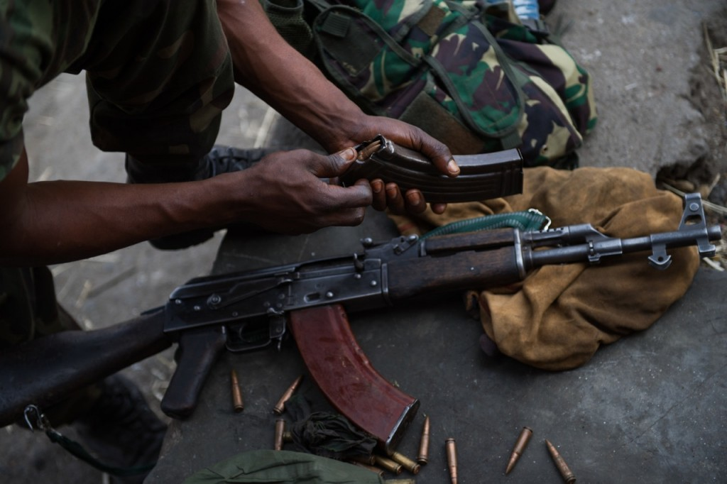 A Congolese army soldier with the FARDC reloads an AK-47 magazine in Monigi, in the outskirts of Goma in the east of the Democratic Republic of the Congo on July 15, 2013. [PHIL MOORE]