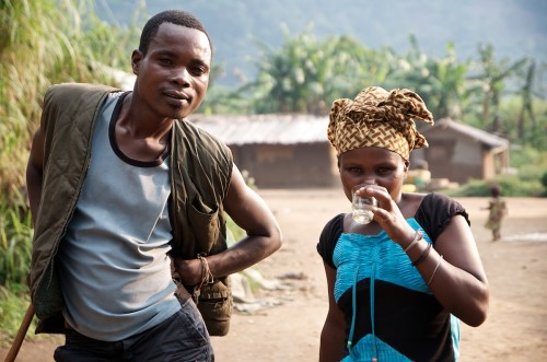 A young woman and an APCLS militiaman (dressed in civilian clothing) getting drunk on kasusu, the local banana-based spirit. Lukweti, Masisi territory, August 2013. ALEXIS BOUVY/ Local Voices