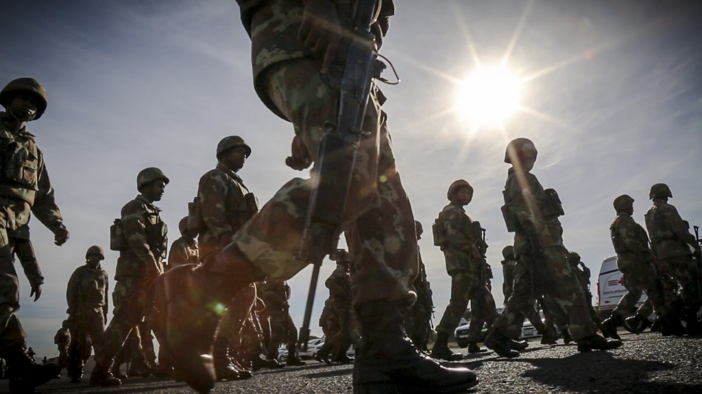 SANDF soldiers, with unloaded assault rifles, walk toward their marshalling point in preparation for a cordon and search operation with police in Bellville, Western Cape.