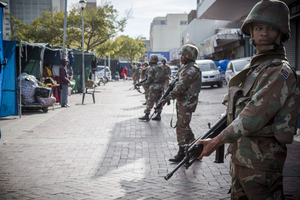 SANDF soldiers maintain a perimeter to allow police to conduct a 'cordon and search' operation in Bellville, Western Cape.