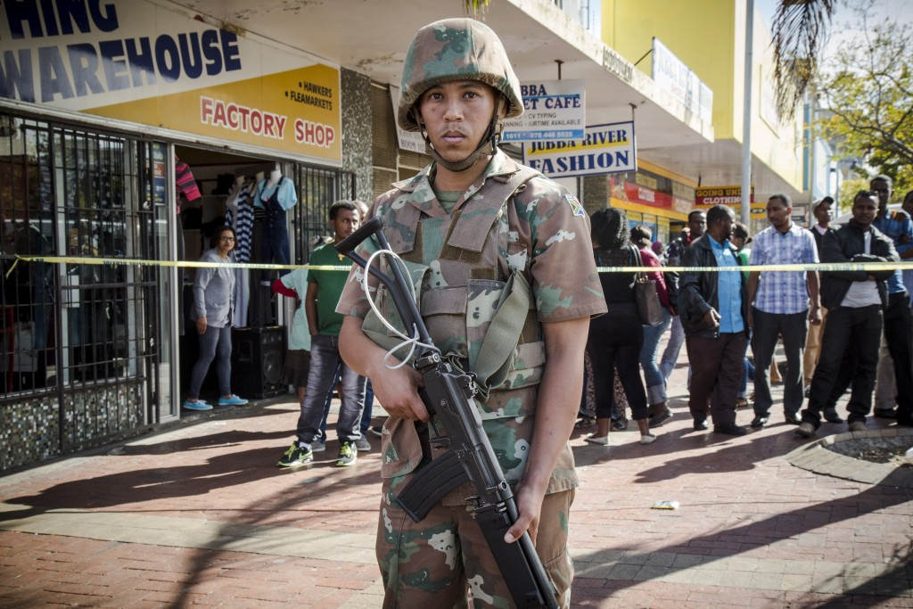 A single SANDF soldiers stands at the perimeter during a police-led cordon and search operation in Bellville, Western Cape. The steel cable, used to attach the soldier's assault rifle to his body to prevent crowds from wrenching it free, is clearly visible. TRENT PERKINS/ADR