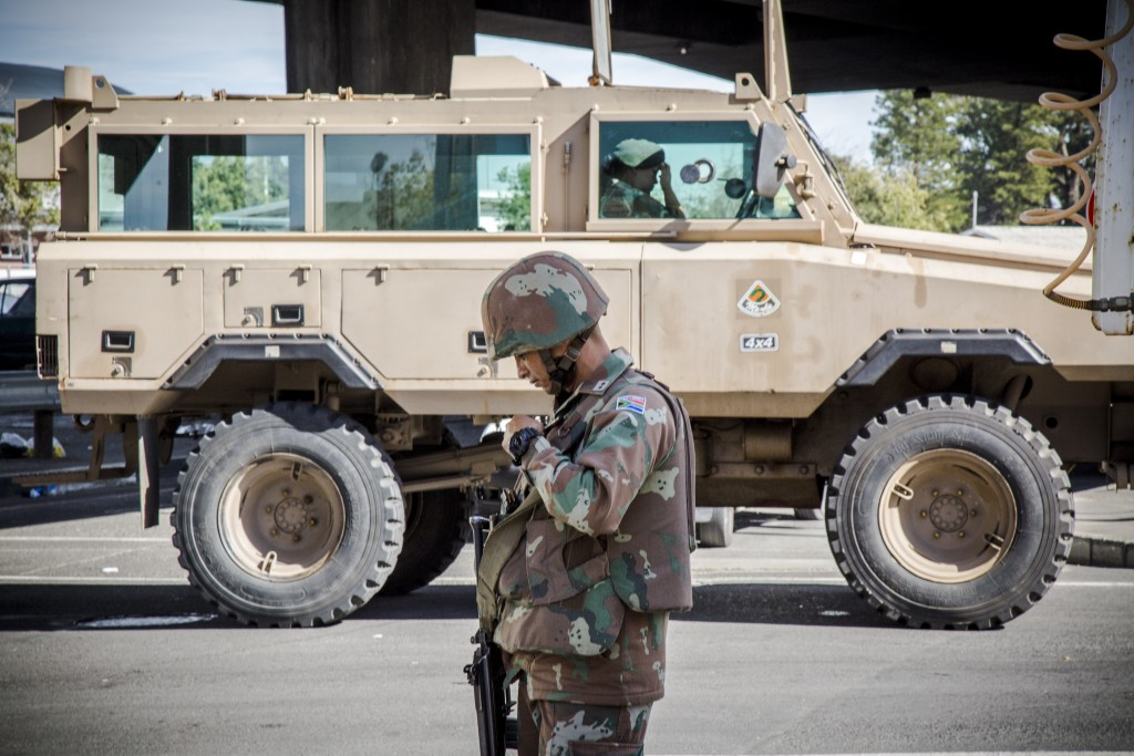 An SANDF soldier stands in front of one of his unit's Mamba armoured personnel carriers during a police-led cordon and search operation in Bellville, Western Cape. TRENT PERKINS/ADR