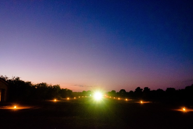 The airstrip dotted with paraffin lanterns with the plane heading towards us