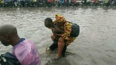 Photo of Gang charge $0.28 to back commuters across flooded road